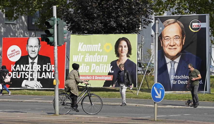 People walk and drive past election posters of the three chancellor candidates, from right, Armin Laschet, Christian Democratic Union (CDU), Annalena Baerbock, German Green party (Die Gruenen), Olaf Scholz, Social Democratic Party (SPD), and Christian Lindner, German Liberals (FDP) at a street in Gelsenkirchen, Germany, Thursday, Sept. 23, 2021 three days before the General election on Sunday, Sept. 26, 2021. (AP Photo/Martin Meissner)