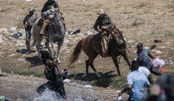 U.S. Customs and Border Protection mounted officers attempt to contain migrants as they cross the Rio Grande from Ciudad Acuna, Mexico, into Del Rio, Texas, Sunday, Sept. 19, 2021. The White House is facing sharp condemnation from Democrats for its handling of the influx of Haitian migrants at the U.S. southern border, after images of U.S. Border Patrol agents on horseback using aggressive tactics went viral. (AP Photo/Felix Marquez)