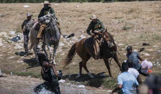 U.S. Customs and Border Protection mounted officers attempt to contain migrants as they cross the Rio Grande from Ciudad Acuna, Mexico, into Del Rio, Texas, Sunday, Sept. 19, 2021. The White House is facing sharp condemnation from Democrats for its handling of the influx of Haitian migrants at the U.S. southern border, after images of U.S. Border Patrol agents on horseback using aggressive tactics went viral. (AP Photo/Felix Marquez) **FILE**