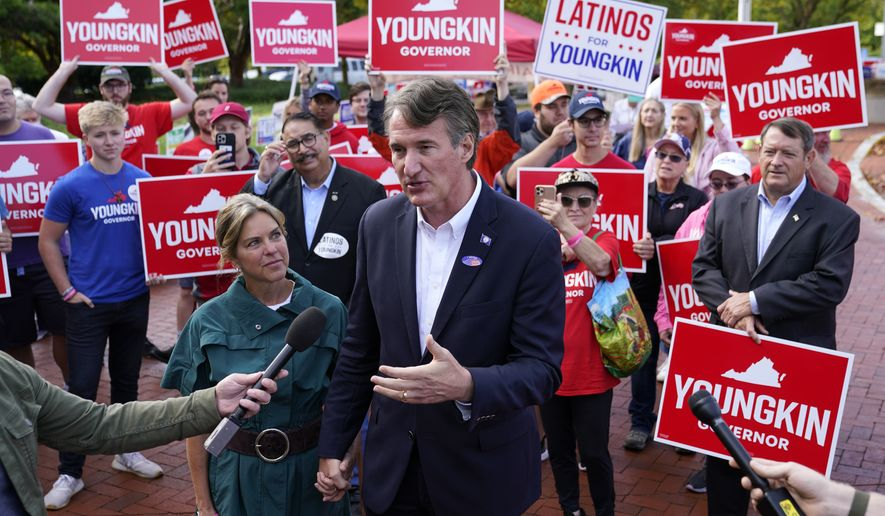Virginia Republican gubernatorial candidate Glenn Youngkin speaks with members of the press alongside his wife Suzanne, left, after voting early, Thursday, Sept. 23, 2021, in Fairfax, Va. (AP Photo/Patrick Semansky)