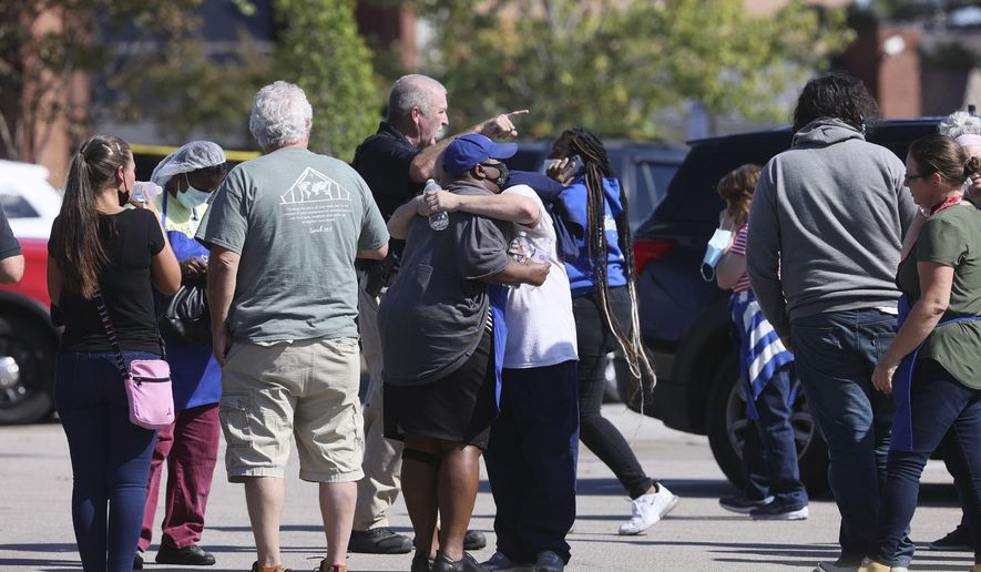 People embrace as police respond to the scene of a shooting at a Kroger's grocery store in Collierville, Tenn., on Thursday, Sept. 23, 2021. (Joe Rondone/The Tennessean via AP)