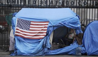 In this March 20, 2020, file photos, a man smokes inside a tent on skid row in Los Angeles. The 9th U.S. Court of Appeals on Thursday, Sept. 23, 2021, overturned a federal judge's sweeping order that required the city and county of Los Angeles to quickly find shelter for all homeless people living on downtown's Skid Row.  (AP Photo/Marcio Jose Sanchez, File) **FILE**