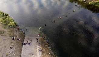 Migrants, many from Haiti, wade back and forth between Texas and Mexico across the Rio Grande, Wednesday, Sept. 22, 2021, in Del Rio, Texas. (AP Photo/Julio Cortez)