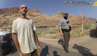 """This Aug. 12, 2021, photo from video provided by The Moab Police Department shows Brian Laundrie talking to a police officer after police pulled over the van he was traveling in with his girlfriend, Gabrielle """"Gabby"""" Petito, near the entrance to Arches National Park. Laundrie, the boyfriend of Gabby Petito, whose body was found at a national park in Wyoming after a cross-country trip with him, has been charged with unauthorized use of a debit card as searchers continue looking for him in Florida swampland, federal authorities announced Thursday, Sept. 23, 2021. (The Moab Police Department via AP) **FILE**"""