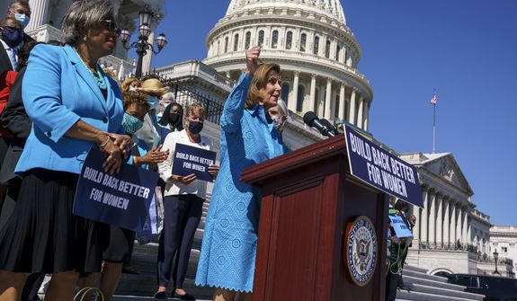 "House Speaker Nancy Pelosi, D-Calif., joined at left by Rep. Brenda Lawrence, D-Mich., holds a rally in support of President Joe Biden's ""Build Back Better"" for women agenda, at the Capitol in Washington, Friday, Sept. 24, 2021. (AP Photo/J. Scott Applewhite)"