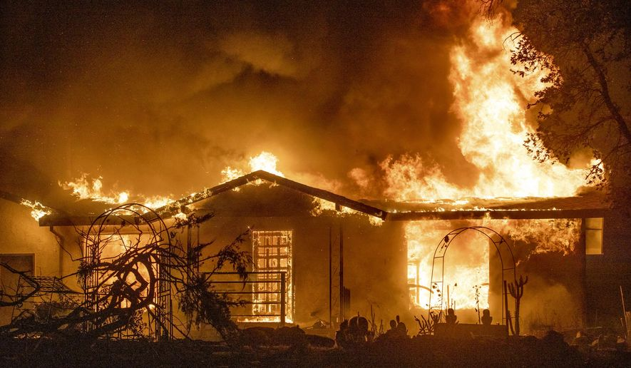 FILE - In this Sept. 27, 2020, file photo, a house burns on Platina Road at the Zogg Fire near Ono, Calif.  Pacific Gas & Electric has been charged with manslaughter and other crimes, Friday, Sept. 24, 2021,  in a Northern California wildfire last year that killed four people and destroyed hundreds of homes.  (AP Photo/Ethan Swope, File)
