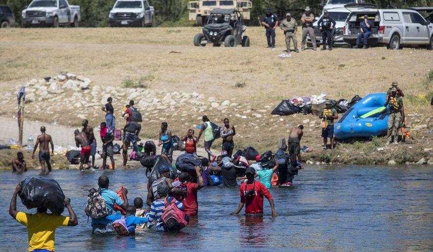 Migrants, most from Haiti, cross the Rio Grande towards Del Rio, Texas, from Ciudad Acuña, Mexico, Thursday, Sept. 23, 2021. (AP Photo/Felix Marquez)