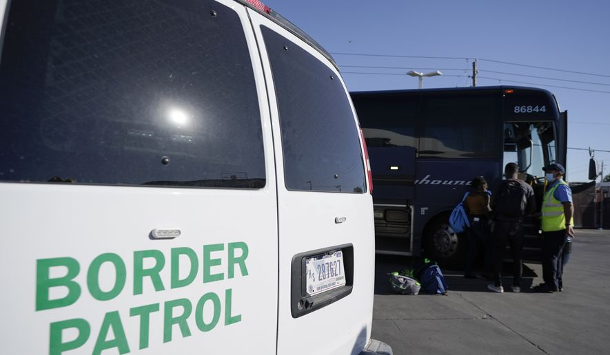 A U.S. Customs and Border Protection van is seen next to a bus picking up travelers, mostly migrants from Haiti released from CBP custody, at a gas station that serves as a bus terminal, Thursday, Sept. 23, 2021, in Del Rio, Texas. Migrants released are greeted by a humanitarian organization, which facilitates bus tickets to San Antonio as they continue their journey. On Friday, the camp on the U.S. side that once held as many as 15,000 mostly Haitian refugees was completely cleared. (AP Photo/Julio Cortez)