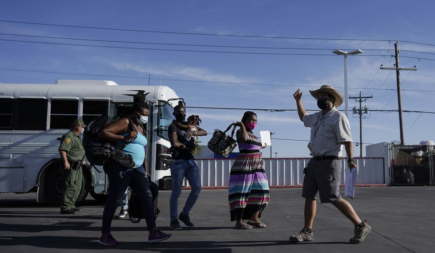 In this Wednesday, Sept. 22, 2021, file photo, a member with the Border Humanitarian Coalition, right, guides migrants, mostly from Haiti, as they are released from United States Border Patrol custody upon crossing the Texas-Mexico border in search of asylum in Del Rio, Texas. (AP Photo/Julio Cortez, File)