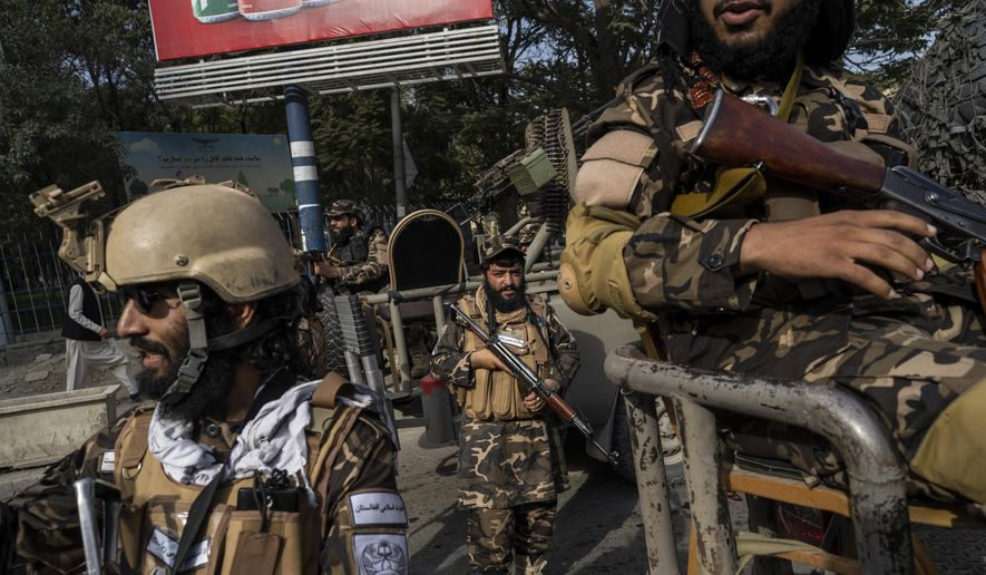 Fighters of the Haqqani network secure an area during a demonstration organised by the Afghan Society of Muslim Youth, demanding the release of frozen international money in Kabul, Afghanistan, Friday, Sept. 24, 2021. Afghanistan faces an economic meltdown after the chaos of the past month, which saw the Taliban oust the government in a lightning sweep as U.S. and NATO forces exited the 20-year war. (AP Photo/Bernat Armangue)