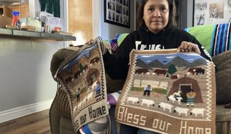 Seraphine Warren poses for a photo in her home in Tooele, Utah, on Sept. 23, 2021, with a rug made by her aunt, Navajo rug weaver Ella Mae Begay. Begay, 62, disappeared in June, one of thousands of missing Indigenous women across the U.S. The extensive coverage of the Gabby Petito case is renewing calls to also shine a spotlight on missing people of color. (AP Photo/Lindsay Whitehurst)
