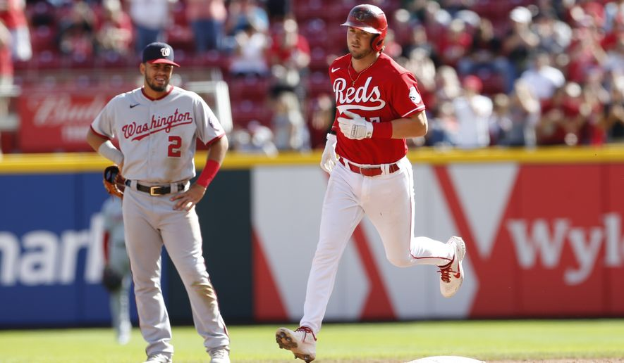 Cincinnati Reds' Kyle Farmer, right, rounds the bases after his grand slam home run against the Washington Nationals during the sixth inning of a baseball game Sunday, Sept. 26, 2021, in Cincinnati. (AP Photo/Jay LaPrete)