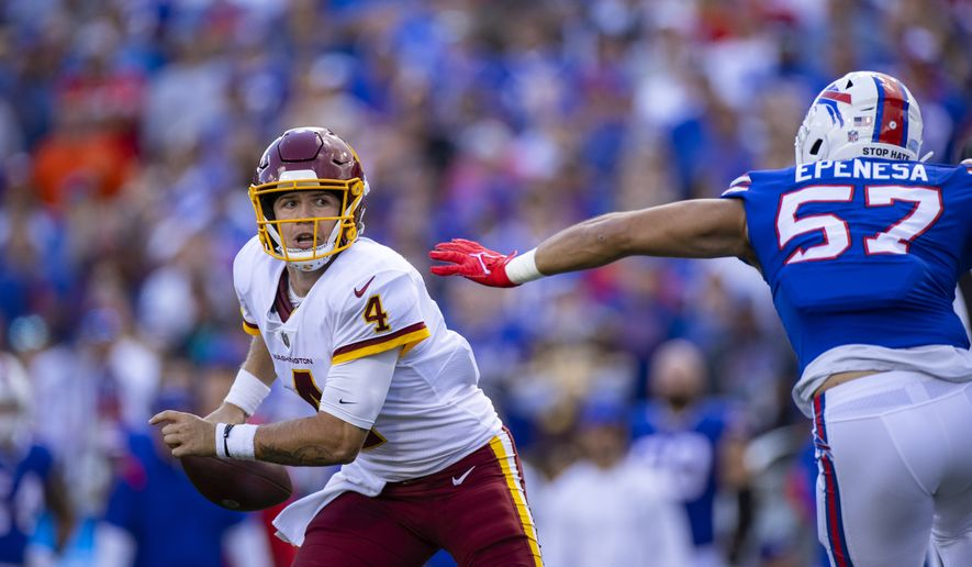 Washington Football Team quarterback Taylor Heinicke (4) flees the pass rush of Buffalo Bills defensive end A.J. Epenesa (57) during the second quarter of an NFL football game, Sunday, Sept. 26, 2021, in Orchard Park, N.Y. (AP Photo/Brett Carlsen)