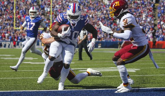 Buffalo Bills running back Zack Moss (20) runs past Washington Football Team's Cole Holcomb (55) for a touchdown as quarterback Josh Allen (17) watches during the first half of an NFL football game Sunday, Sept. 26, 2021, in Orchard Park, N.Y. (AP Photo/Jeffrey T. Barnes)
