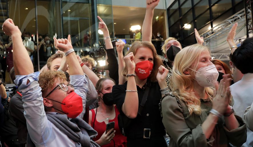 Supporters react after German parliament election at the Social Democratic Party, SPD, headquarters in Berlin, Sunday, Sept. 26, 2021. (AP Photo/Lisa Leutner)