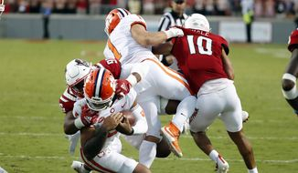 North Carolina State's Savion Jackson (90) tackles Clemson's D.J. Uiagalelei (5) as the left leg of Clemson running back Will Shipley (1) gets caught with North Carolina State's Tanner Ingle (10) also defending during the second half of an NCAA college football game in Raleigh, N.C., Saturday, Sept. 25, 2021. (AP Photo/Karl B DeBlaker) **FILE**