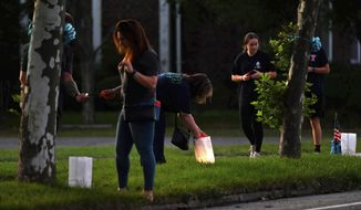 People light candles along Blue Point Ave. in Blue Point, NY in memory of Gabby Petito, Friday, Sept. 24, 2021.  Federal officials say Brian Laundrie, the boyfriend of Petito, whose body was found at a national park in Wyoming after a cross-country trip with him, has been indicted for unauthorized use of a debit card. (Steve Pfost/Newsday via AP)