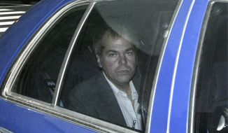 FILE - In this Nov. 18, 2003, file photo, John Hinckley Jr. arrives at U.S. District Court in Washington. Lawyers are scheduled to meet in federal court on Monday, Sept. 27, 2021 to discuss whether Hinckley Jr., the man who tried to assassinate President Ronald Reagan, should be freed from court-imposed restrictions including overseeing his medical care and keeping up with his computer passwords. (AP Photo/Evan Vucci, File)