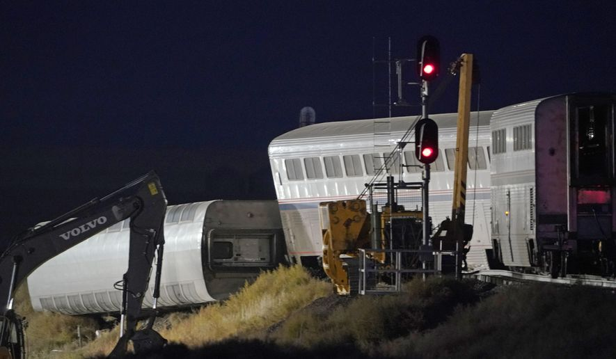 Cars from an Amtrak train that derailed the day before are shown illuminated by floodlights, late Sunday, Sept. 26, 2021, as they rest near a train signal near Joplin, Mont. The westbound Empire Builder was en route to Seattle from Chicago with two locomotives and 10 cars. (AP Photo/Ted S. Warren)