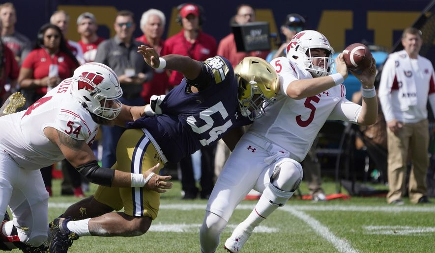 Wisconsin quarterback Graham Mertz (5) makes a two-handed pass to avoid the pressure from Notre Dame defensive lineman Jacob Lacey after Lacey got past lineman Kayden Lyles during the first half of an NCAA college football game Saturday, Sept. 25, 2021, in Chicago. (AP Photo/Charles Rex Arbogast) **FILE**