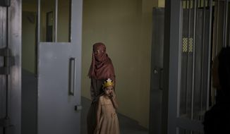 Razia and her 6-year-old daughter Alia, stand inside the women's section of the Pul-e-Charkhi prison in Kabul, Afghanistan, Thursday, Sept. 23, 2021. When the Taliban took control of a northern Afghan city of Pul-e-Kumri the operator of the only women's shelter ran away, abandoning 20 women in it. When the Taliban arrived at the shelter the women were given two choices: Return to their abusive families, or go with the Taliban, With nowhere to put the women, the Taliban took them to the abandoned women's section of Afghanistan's notorious Pul-e-Charkhi prison. (AP Photo/Felipe Dana)