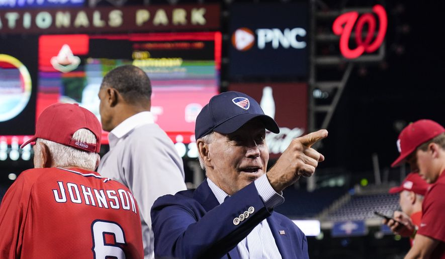 President Joe Biden points to a fan from the Republican dugout during the Congressional Baseball Game at Nationals Park Wednesday, Sept. 29, 2021, in Washington. The annual baseball game between congressional Republicans and Democrats raises money for charity. (AP Photo/Alex Brandon)