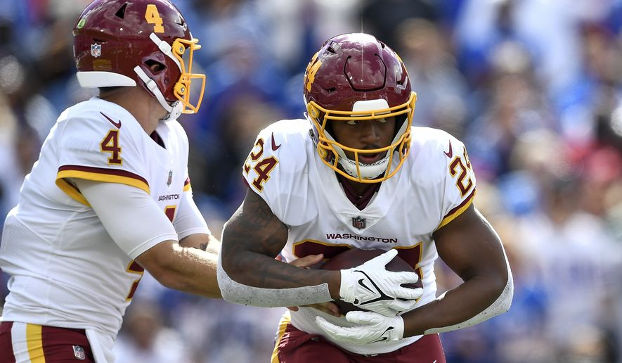 Washington Football Team running back Antonio Gibson, right, takes a handoff from quarterback Taylor Heinicke during the first half of an NFL football game Sunday, Sept. 26, 2021, in Orchard Park, N.Y. (AP Photo/Adrian Kraus)
