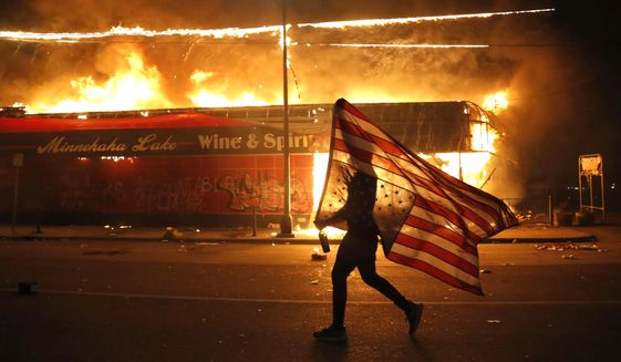 In this May 28, 2020, file photo, a protester carries an American flag upside down, a sign of distress, next to a burning building in Minneapolis. (AP Photo/Julio Cortez, File)