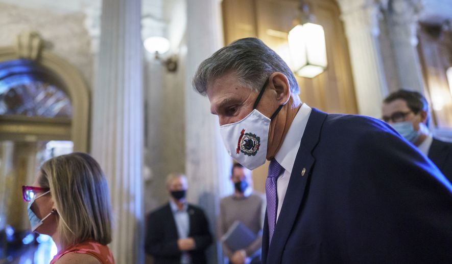 Sen. Joe Manchin, D-W.Va., and Sen. Kyrsten Sinema, D-Ariz., far left, arrive to vote on a temporary government funding bill to avert a shutdown, at the Capitol in Washington, Thursday, Sept. 30, 2021. President Joe Biden appears unable to strike swift agreement with the two wavering Democrats who are pivotal votes for his big $3.5 trillion government overhaul. (AP Photo/J. Scott Applewhite)