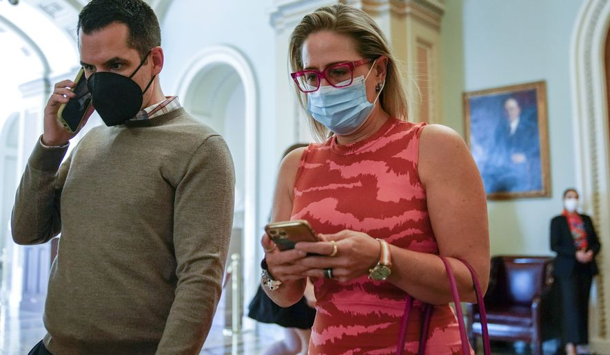 Sen. Kyrsten Sinema, D-Ariz., walks out of the Senate Chamber on Capitol Hill in Washington, Thursday, Sept. 30, 2021. (AP Photo/Patrick Semansky)