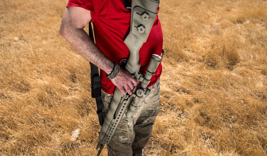 Firearms instructor Michael Palombo holds a Springfield Armory M25 rifle during field testing to measure radio frequency identification signal range in Hickman, Calif., on Sunday, June 6, 2021. Palombo inserted an RFID tag into the rifle for the test. (AP Photo/Noah Berger)