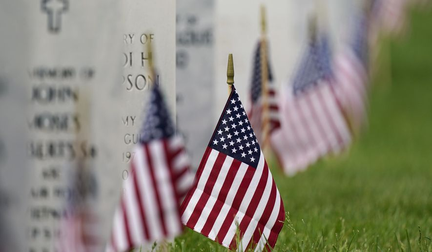 In this May 31, 2021 file photo, flags and tributes mark the Memorial Day holiday at Fort Logan National Cemetery in southeast Denver. The number of U.S. military suicides jumped by 15% last year, fueled by significant increases in the Army and Marine Corps that senior leaders called troubling. They urged more effort to reverse the trend. (AP Photo/David Zalubowski)
