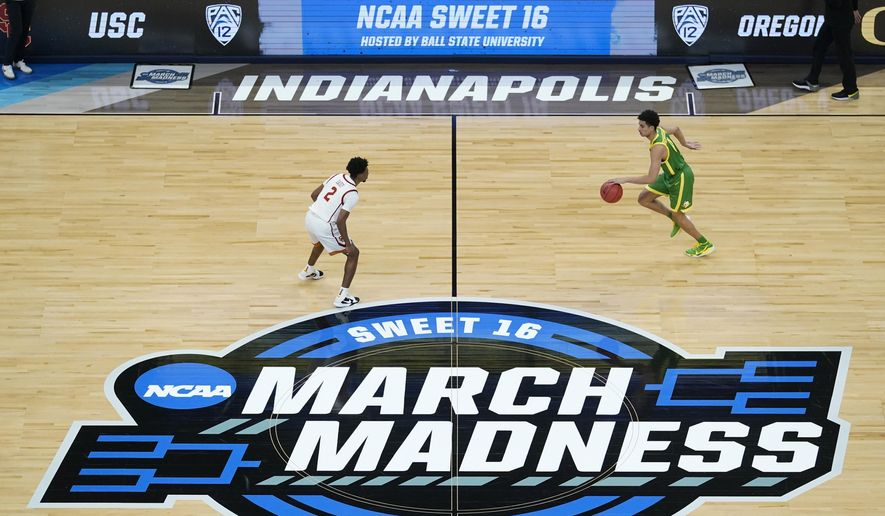 Oregon guard Will Richardson, right, drives up court in front of Southern California guard Tahj Eaddy (2) during the first half of a Sweet 16 game in the NCAA men's college basketball tournament at Bankers Life Fieldhouse in Indianapolis, in this Sunday, March 28, 2021, file photo. The NCAA women's basketball tournament will use March Madness in marketing and branding beginning this season. Using the phrase, which has been associated with the men's tournament for years, was one of the recommendations from an external review of gender equity issues of the tournaments that was released in August.  (AP Photo/Darron Cummings, File). **FILE**