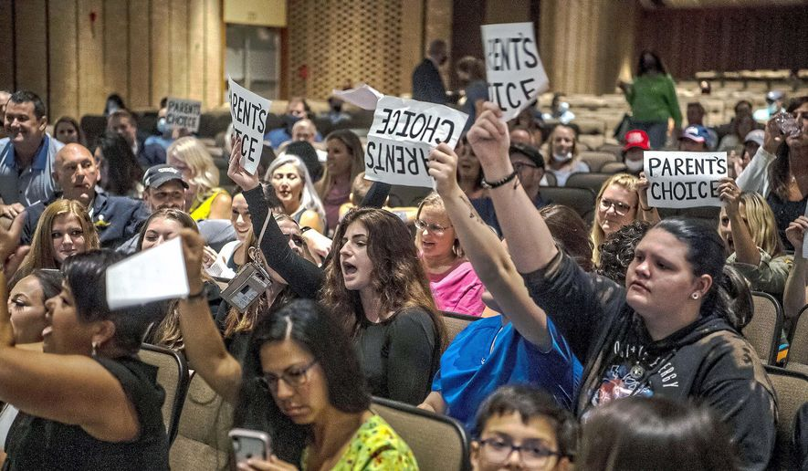 In this Aug. 25, 2021, file photo, people hold signs and chant during a meeting of the North Allegheny School District school board regarding the district's mask policy, at at North Allegheny Senior High School in McCandless, Pa. The nation's school boards are asking President Joe Biden for federal assistance to investigate and stop a growing number of threats made against their members, on Thursday, Sept. 30. (Alexandra Wimley/Pittsburgh Post-Gazette via AP, File)