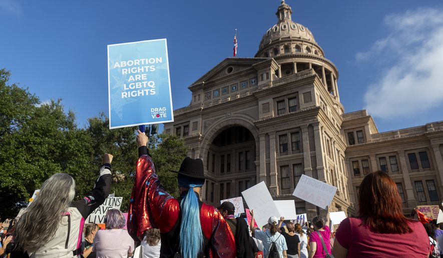 People attend the Women's March ATX rally, Saturday, Oct., 2, 2021, at the Texas State Capitol in Austin, Texas. The march was a response to controversial legislation recently passed by Texas lawmakers which has banned most abortions in Texas.  (AP Photo/Stephen Spillman)