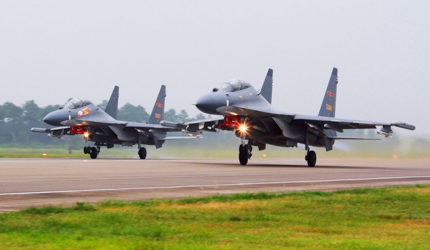 In this undated file photo released by China's Xinhua News Agency, two Chinese SU-30 fighter jets take off from an unspecified location to fly a patrol over the South China Sea. China flew more than 30 military planes, including SU-30 fighter jets, toward Taiwan on Saturday, Oct. 3, 2021, the second large display of force in as many days.(Jin Danhua/Xinhua via AP, File)