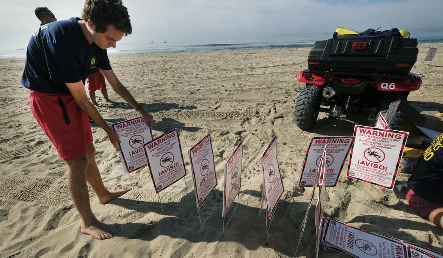 Lifeguards ready to post signs warning that water contact may cause illness, as they close the beach after an oil spill in Huntington Beach, Calif., Sunday., Oct. 3, 2021. The closure stretched from the Huntington Beach Pier nearly 4 miles (6.4 kilometers) south to the Santa Ana River jetty amid summerlike weather that would have brought beachgoers to the wide strand for volleyball, swimming and surfing. Yellow caution tape was strung between lifeguard towers to keep people away. (AP Photo/Ringo H.W. Chiu)