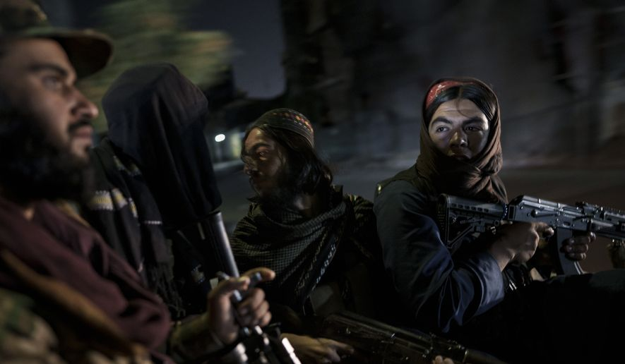 Taliban fighters ride in the back of a vehicle during a night patrol in Kabul, Afghanistan, Sunday, Sept. 12, 2021. The Taliban are shifting from being warriors to an urban police force. (AP Photo/Felipe Dana) ** FILE **