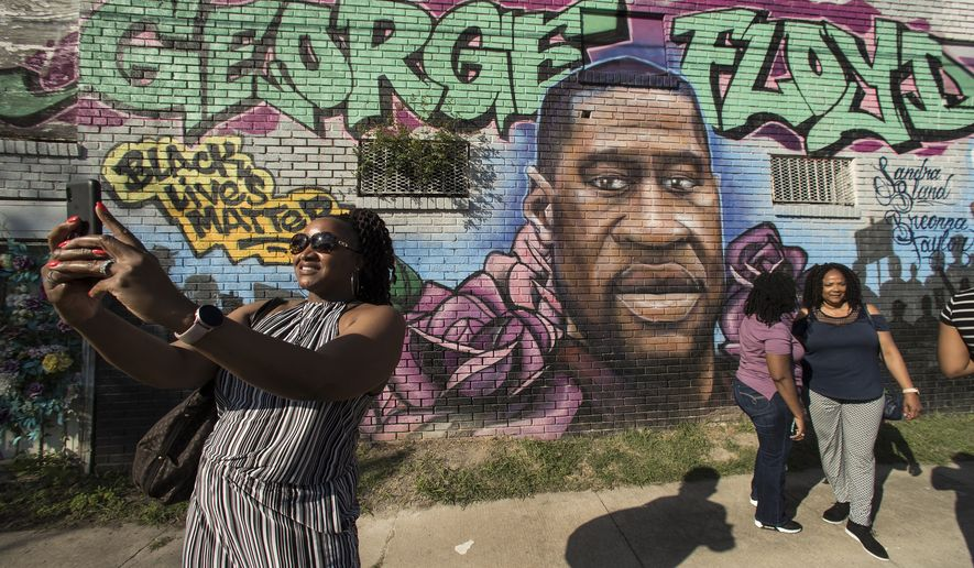 FIn this Tuesday, April 20, 2021, file photo, Laynette Jacob takes a photo in front of a George Floyd mural with her friends near the intersection of Elgin and Ennis as she joins others as they react after learning of the guilty verdict on all counts in the murder trial of former Minneapolis police Officer Derek Chauvin in the death of George Floyd, in Houston. In an announcement on Monday, Oct. 4, 2021, a Texas agency has approved a request that Floyd be granted a posthumous pardon for a 2004 drug arrest made by a now-indicted ex-Houston police officer whose case history is under scrutiny following a deadly drug raid. (Brett Coomer/Houston Chronicle via AP, File)