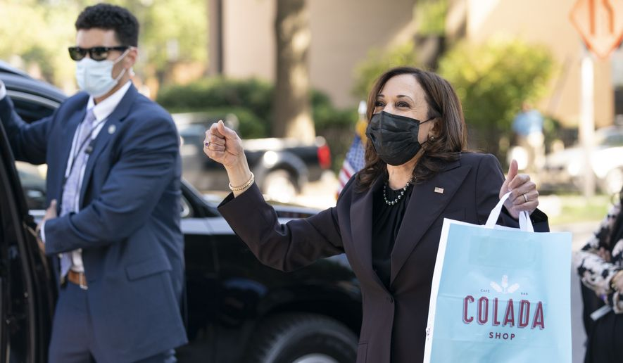 Vice President Kamala Harris reacts to people waving as she exits The Colada Shop, a Latina owned coffee shop, Monday, Oct. 4, 2021, in Washington. (AP Photo/Jacquelyn Martin)