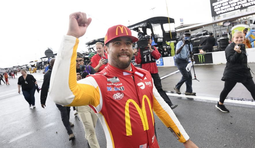 Bubba Wallace celebrates after being pronounced the winner while waiting out a rain delay before which he was the leader in a NASCAR Cup series auto race Monday, Oct. 4, 2021, in Talladega, Ala. (AP Photo/John Amis)