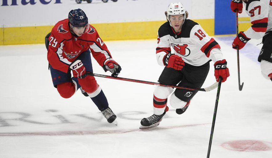 New Jersey Devils forward Dawson Mercer (18) skates with the puck ahead of Washington Capitals center Hendrix Lapierre (29) during the second period of an NHL preseason hockey game, Wednesday, Sept. 29, 2021, in Washington. (AP Photo/Nick Wass) **FILE**