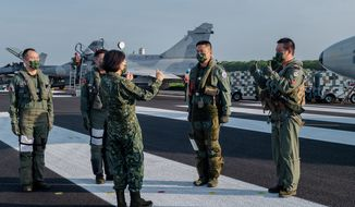 In this photo released by the Taiwan Presidential Office, Taiwanese President Tsai Ing-wen, center, speaks with military personnel near aircraft parked on a highway in Jiadong, Taiwan, Wednesday, Sept. 15, 2021. Four military aircraft landed on the highway and took off again on Wednesday as part of Taiwan's five-day Han Guang military exercise designed to prepare the island's forces for an attack by China, which claims Taiwan as part of its own territory. (Taiwan Presidential Office via AP) ** FILE **