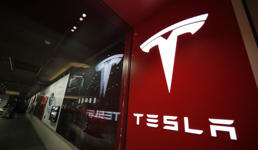 In this Feb. 9, 2019, file photo, a sign bearing the company logo stands outside a Tesla store in Cherry Creek Mall in Denver. U.S. automobile safety regulators have denied a petition seeking an investigation into Tesla software updates, saying it's unlikely a probe would show there's a safety defect. The National Highway Traffic Safety Administration on Monday, Oct. 4, 2021, denied the 2019 petition, which alleged that over-the-internet software updates cut battery range in response to battery fires across the globe. (AP Photo/David Zalubowski, file)