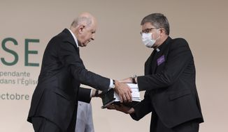 Commission President Jean-Marc Sauve, left, hands copies of the report to Catholic Bishop Eric de Moulins-Beaufort, president of the Bishops' Conference of France (CEF), during the publishing of a report by an independent commission into sexual abuse by church officials (Ciase), Tuesday, Oct. 5, 2021, in Paris. A major French report released Tuesday found that an estimated 330,000 children were victims of sex abuse within France's Catholic Church over the past 70 years, in France's first major reckoning with the devastating phenomenon. (Thomas Coex, Pool via AP)