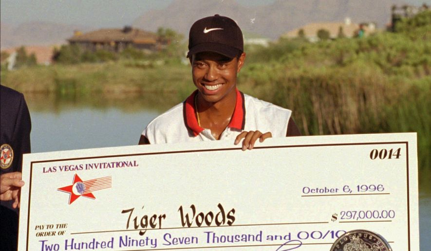 In this Oct. 6, 1996, file photo, rookie pro golfer Tiger Woods smiles after receiving a check and trophy for winning the Las Vegas Invitational golf tournament at TPC at Summerlin in Las Vegas. Twenty-five years ago this week Woods won for the first time on the PGA Tour at the Las Vegas Invitational, changing golf forever. (AP Photo/Lennox McLendon, File) **FILE**