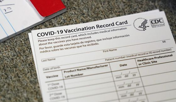 FILE - In this Dec. 24, 2020, file photo, a COVID-19 vaccination record card is shown at Seton Medical Center in Daly City, Calif. Los Angeles leaders are poised to enact one of the nation's strictest vaccine mandates, a sweeping measure that would require the shots for everyone entering a bar, restaurant, nail salon, gym or even a Lakers game. The City Council on Wednesday, Oct. 6, 2021, is scheduled to consider the proposal and most members have said they support it as a way of preventing further COVID-019 surges. (AP Photo/Jeff Chiu, File)