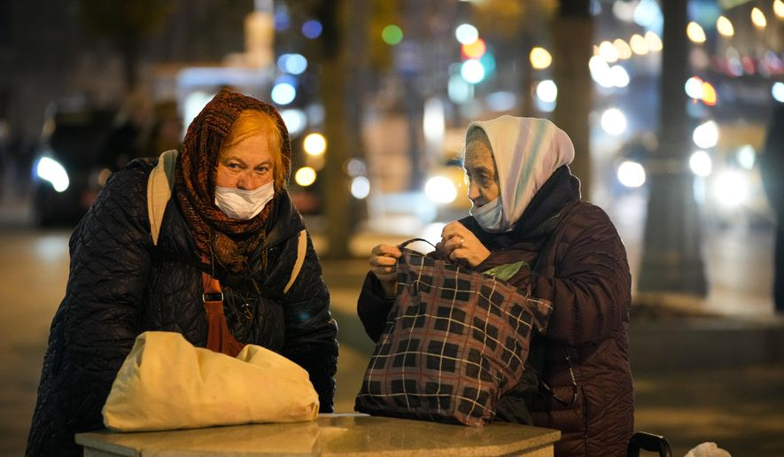 Two elderly women wearing face masks to protect against the coronavirus talk to each other near Red Square in Moscow, Russia, Sunday, Oct. 3, 2021. The Russian authorities have reported 25,781 new coronavirus infections on Monday, Oct. 4, 2021, the largest daily tally since early January. The state coronavirus task force also registered 883 new deaths. The surge in cases comes as vaccination rates in the country remain stagnantly low and the government shuns imposing tough restrictions to stem the spread of the virus. (AP Photo/Alexander Zemlianichenko)