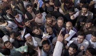 People gather outside a government passport office recently re-opened after Taliban announced they would be issuing a backlog of applications approved by the previous administration in Kabul, Afghanistan, Wednesday, Oct. 6, 2021. (AP Photo/Felipe Dana)