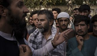 A member of the Taliban, left, talks to Afghans gathering outside a government passport office recently re-opened after Taliban announced they would be issuing a backlog of applications approved by the previous administration in Kabul, Afghanistan, Wednesday, Oct. 6, 2021. (AP Photo/Felipe Dana)